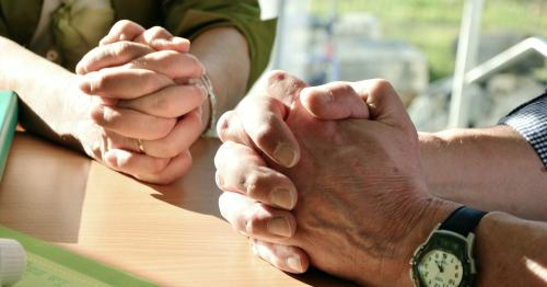 Picture of hands of two people praying.