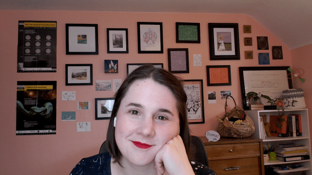 Selfie of me (white lady with straight, short, brown hair and red lipstick) looking at the camera with my cheek resting on my hand. There is a gallery wall of art and conference posters behind me.