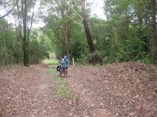 Pushing bike up hilly terrain in loose gravel