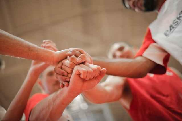 basketball team stacking hands together