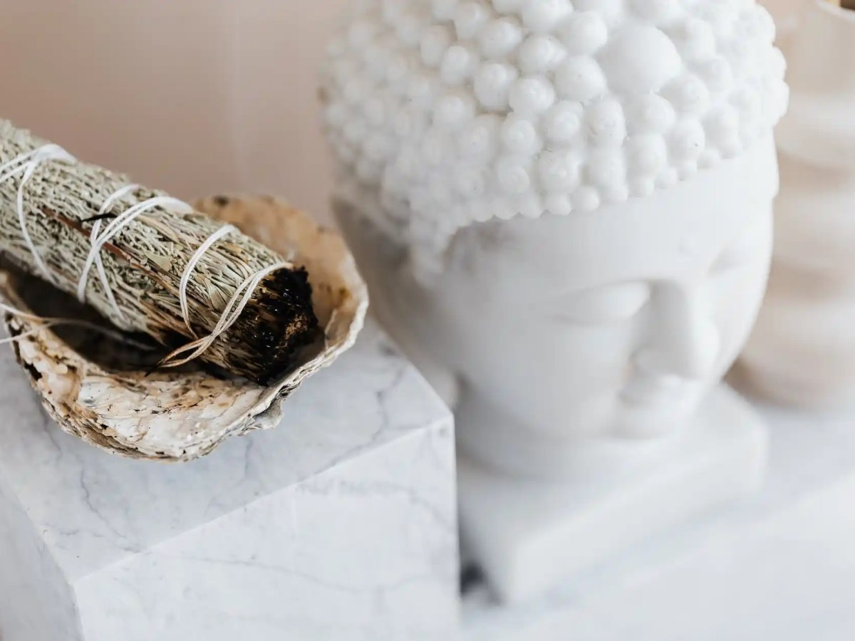 sage smudge stick in bowl on marble shelf near buddha head
