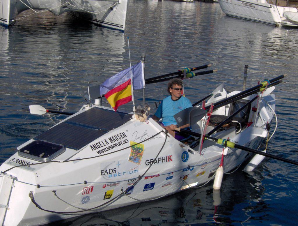 Angela Madsen rowing a craft designed for ocean crossings. www.rowoflife.net is on the hull.