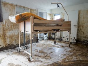 Hochgefahrenes und verdrecktes Pflegebett in einem schlammigen Zimmer in einem vom Hochwasser getroffenem Haus.