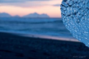 Eis am Strand, im Hintergrund die Berge von Höfn