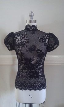 Black lace blouse with a high collar that tapers gently in the back. Has a keyhole at center back with a small button, side invisible zipper entry.