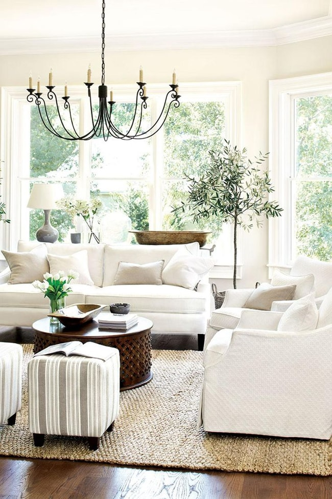 How to decorate with neutral colors: Who said neutral had to be boring? This all-white furniture looks amazing against those large windows filled with green. The pops of color throughout make it feel fresh and clean.
