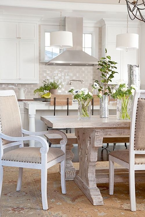 All- white kitchens work best when complimented with colors. This neutral color scheme on the chairs, carpet, and beautiful wood dining table make this kitchen look bright and welcoming.