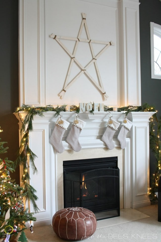 Christmas Mantels - white mantel with wooden star, green pine garland, grey stockings with gold ornaments - Just the Bees Knees