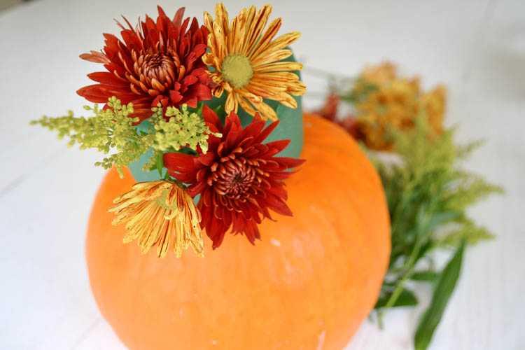 A super cute and simple DIY pumpkin centerpiece idea perfect for a fall table or Thanksgiving table idea! See more on https://ablissfulnest.com/ #falltable #pumpkinideas #falldecor
