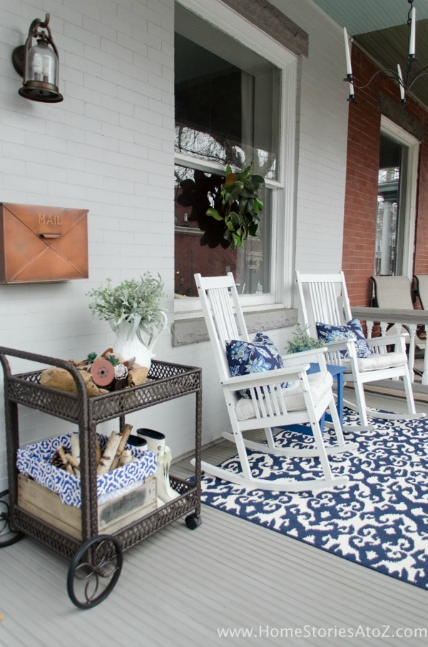 This spring front porch is decorated with a blue theme. White rocking chairs have blue floral patterned throw pillows. A vintage tea cart holds small planters, rain boots, and spring decor. A white and blue oriental pattern rug sits in the center of the porch.