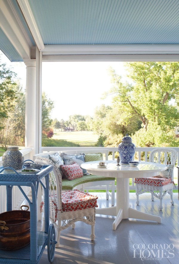 This spring front porch is decorated with beautiful white furniture. The cushions on the chairs are a red, blue, and white floral fabric, accented with pops of green. A periwinkle blue tea cart holds ceramic planters and a vintage washing tub. There is a blue oriental patterned urn on the table.