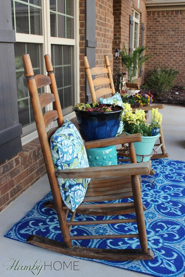 This spring front porch is packed with bright blues. The dark wooden rocking chairs have blue floral fabric throw pillows. Dark and light blue planters hold blooming flowers. A blue fleur-de-lis rug sits in the center.