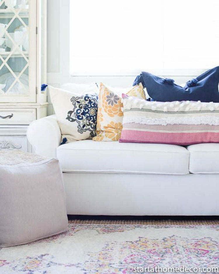 Mixing different patterns and textures of throw pillows is great if you find one element, like complimenting colors to bring the look together like this white couch styled with four different throw pillows