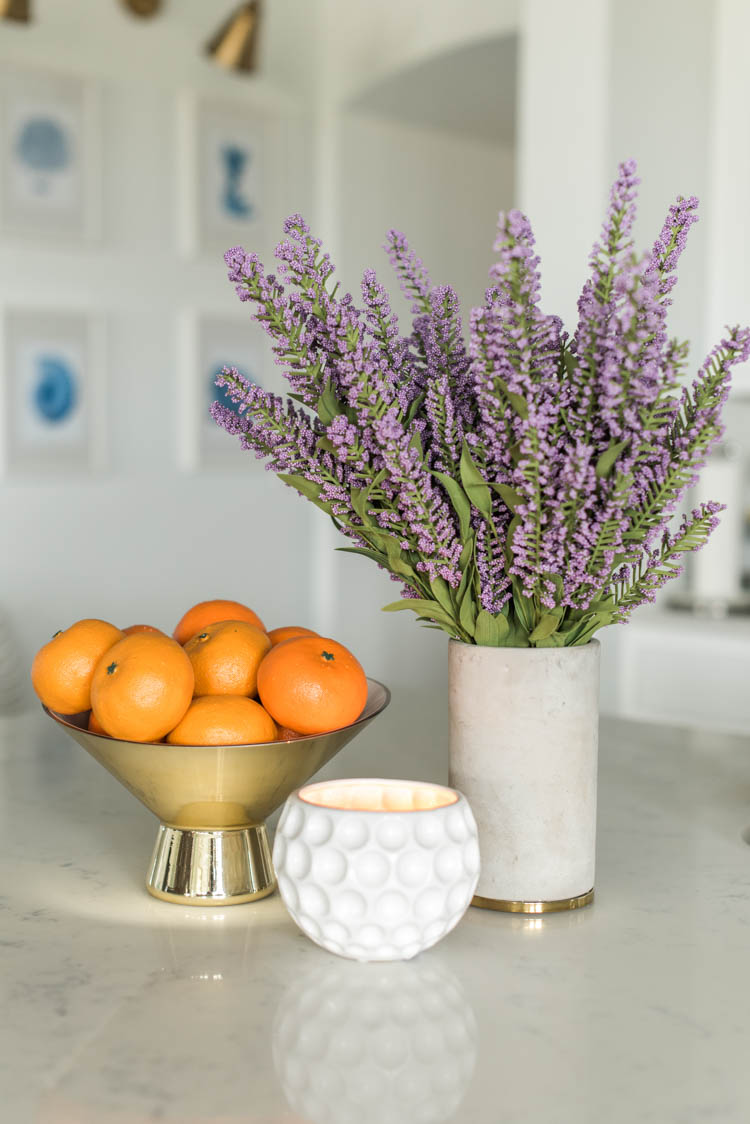 Spring touches are easy to add to a kitchen with accessories like a bowl full of oranges and faux flowers. #ad #AthomeStores #springdecorating #springdecoratingideas #kitchen #springkitchen #whitekitchen