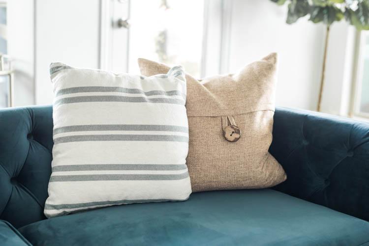 Use accent pillows for some spring flare! #ad #AthomeStores #springdecorating #springdecoratingideas #coastallivingroom