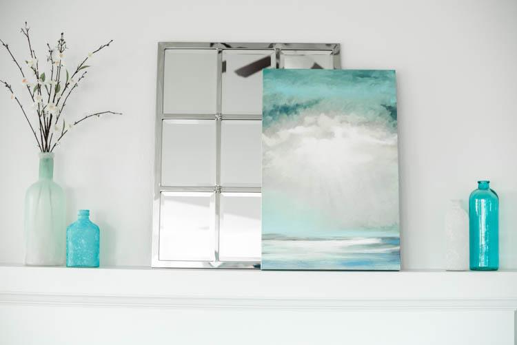 Turquoise accents and a pretty ocean art print. #ad #AthomeStores #springdecorating #springdecoratingideas #coastallivingroom