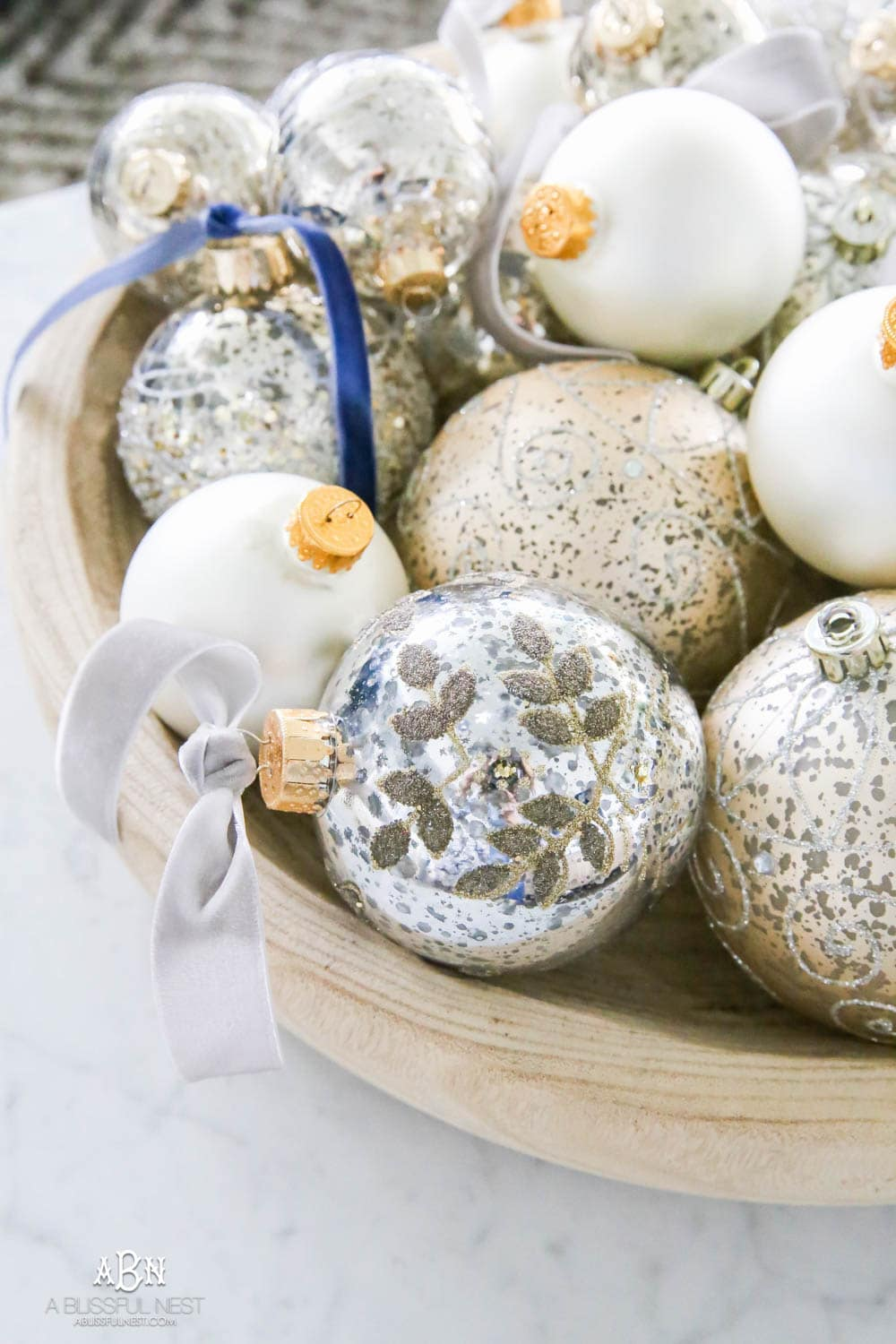 Mercury glass ornaments with velvet ribbons tied and collected in a wood bowl on a coffee table for a gorgeous holiday décor display. Simple touches for Christmas décor that make big impact. Check out all the white, silver and gold Christmas decor in this holiday home tour on ABlissfulNest.com. #ABlissfulNest #Christmasdecor #Christmasdecorating #CoastalChristmasdecor #christmastree #christmasmantle