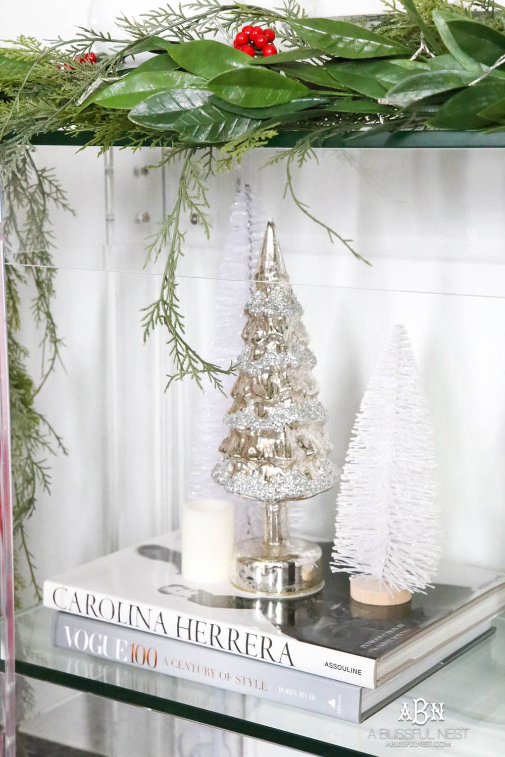 Create a display with your mini trees by clustering them on top of décor books and adding in candles. More ways to add in classic Christmas décor into your home on ablissfulnest.com. #christmasentryway #christmasentry #christmasentrydecor #christmasentrywayideas #christmashometour