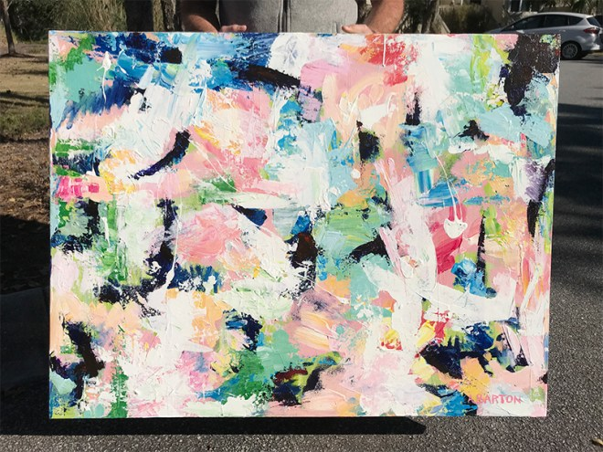 picture of abstract painting being held by someone in a parking lot