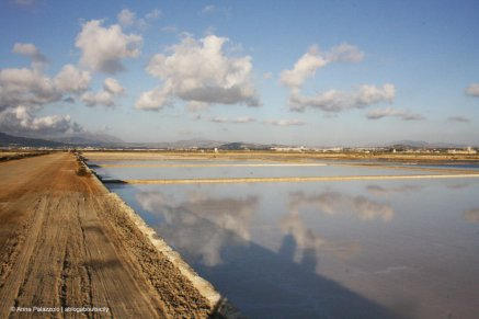 clouds mirrored in the salt pan pools