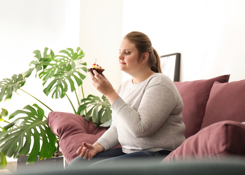 Beautiful plus size girl with sweet cake at home. Concept of body positivity Andreas Mittlböck Abnehmen Gesundheit