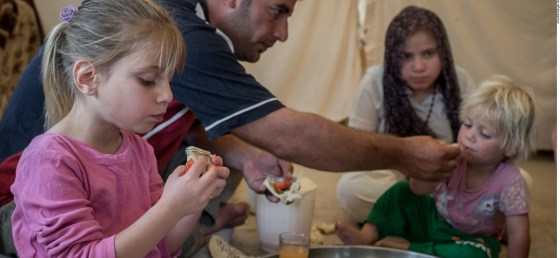 A displaced family from Mosul eat lunch at Baharka Camp on the outskirts of Erbil, Iraq.