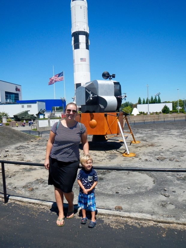 Natalie and Sully with a lunar lander and Saturn V rocket in Huntsville