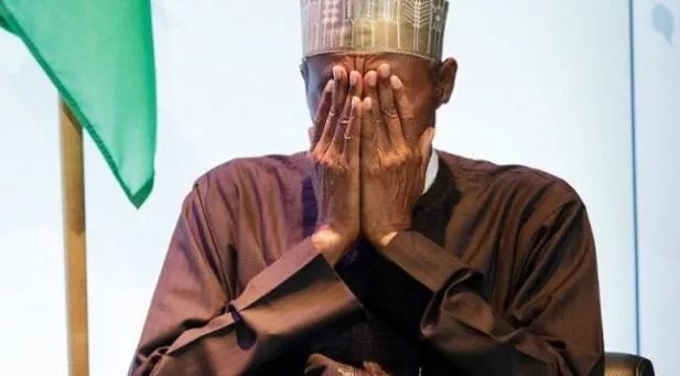 President Buhari covers his face with his hands