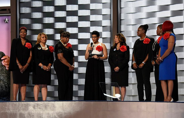 MOTHERS OF THE MOVEMENT, appearing at the 2016 Democratic National Convention in Philadelphia, PA. (MARIA HAMILTON, WANDA JOHNSON, GWEN CARR, GENEVA REED-VEAL, LUCIA MCBATH, SYBRINA FULTON, CLEOPATRA PENDLETON, and LEZLEY MCSPADDEN). The picture is a Creative Commons licensed image from ABC / Ida Mae Astute (via Flickr).