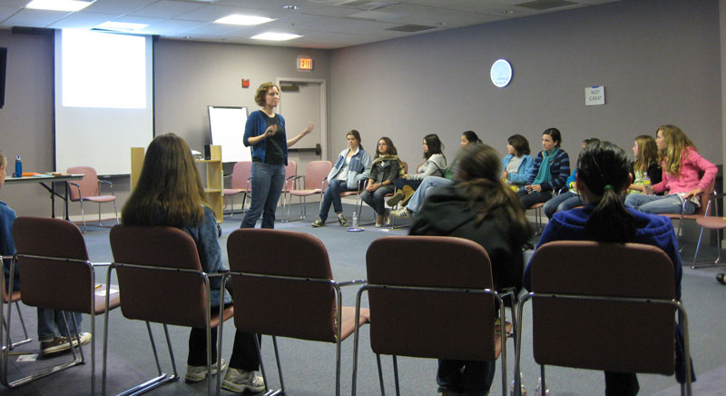 A group of teen girls are seated on chairs in a circle. A woman is standing in front of the group and speaking.