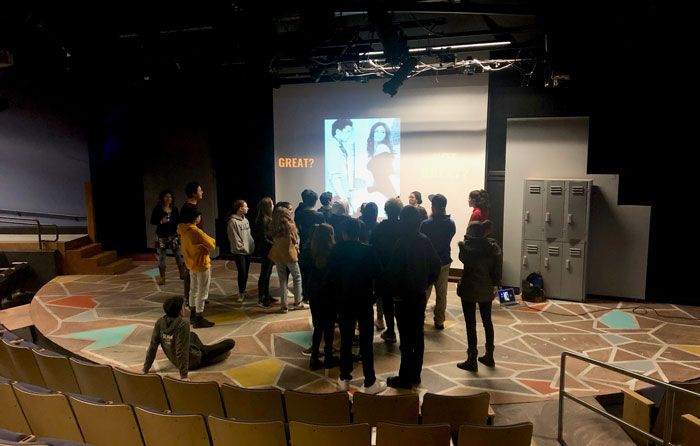 A group of teen students stand on a stage, looking at a large projector screen.