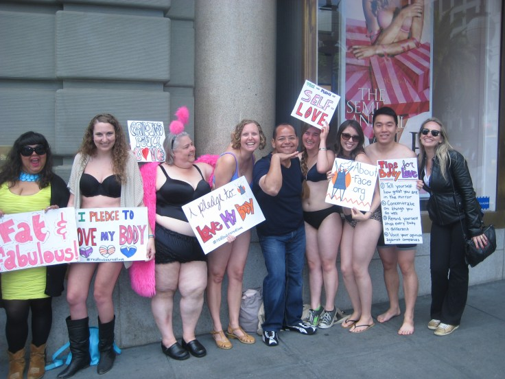 A group of women and men with diverse body types in front of Victoria's Secret in San Francisco.