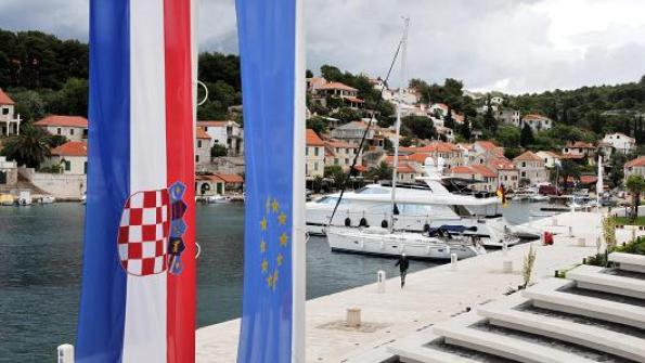 Bryn Colton I Bloomberg via Getty Images The Croatian national flag, left, sits alongside the European Union one