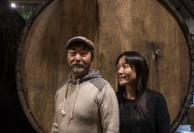 The siblings Peter and Susan Yi in front of one of the casks at their new Brooklyn Cider House in Bushwick. Credit Victor J. Blue for The New York Times