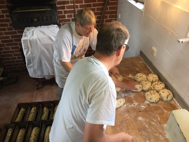 Die beiden Bäckermeister formen die den Brotteig zu Laiben und legen sie zum Ruhen in den Kastenformen.