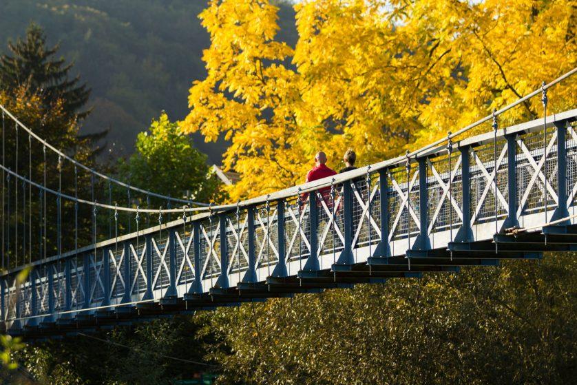 Fußgänger auf der blauen Hängebrücke über der Werra, Herbstlaub im Hintergrund