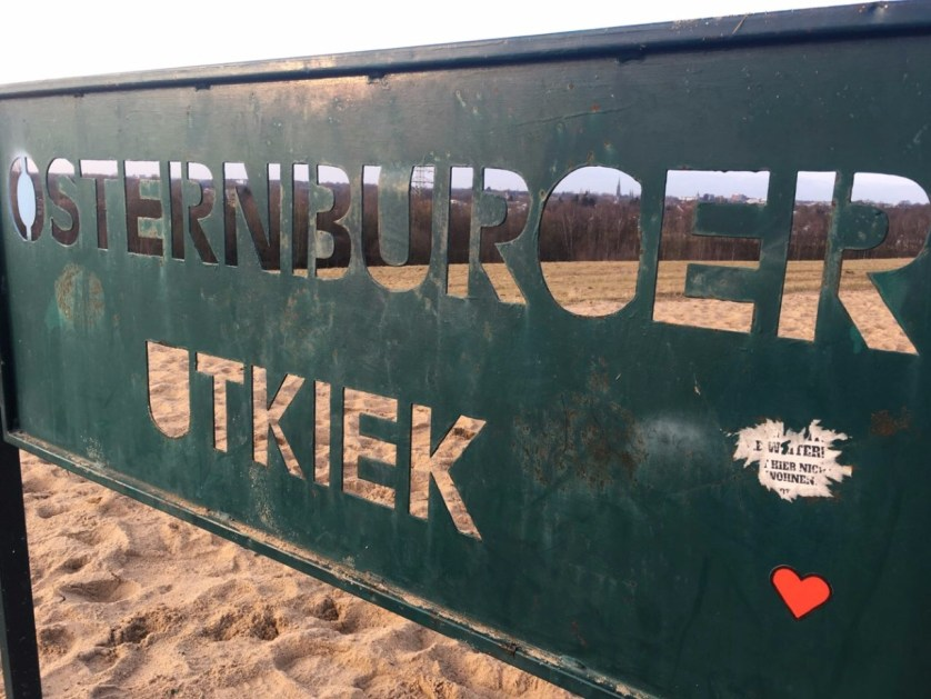 Schaut man durch den Schriftzug sieht man die Silhouette der Stadt Oldenburg