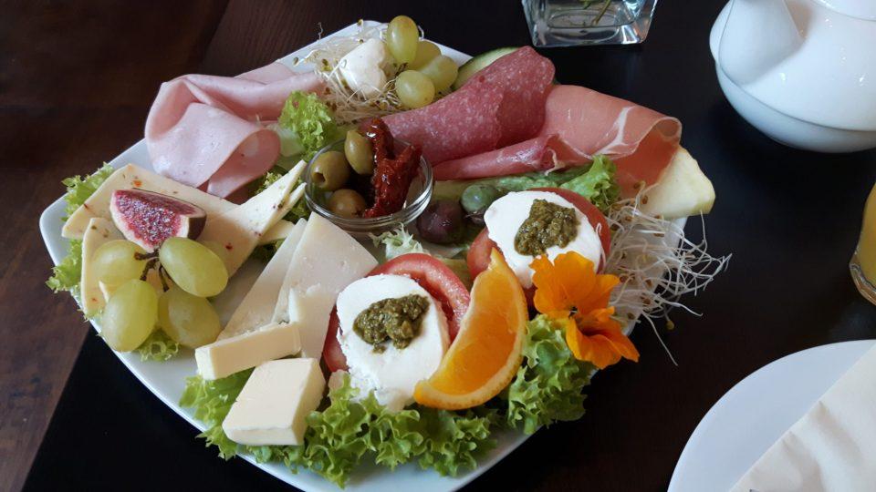 Italienisches Frühstück - ein reich gedeckter Teller mit Käse, Wurst, Antipasti, Tomaten und Mozzarella, unv vielem mehr