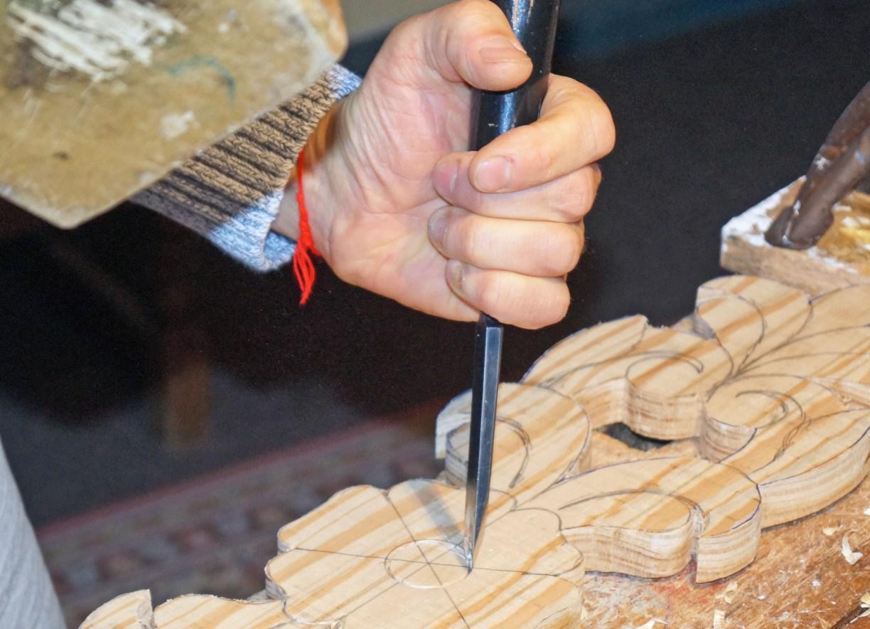 Detailaufnahme von Holzschnitzer Yuri Kulbabenko mit Holzhammer und Beitel bei der Bearbeitung einer Tür-Verzierung