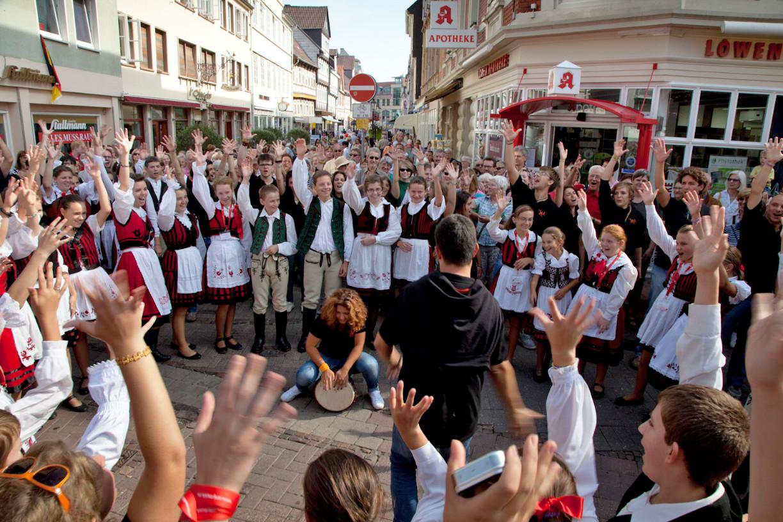 Jugendchor mit Trachtenkleidung und Zuschauern in der Fußgängerzone
