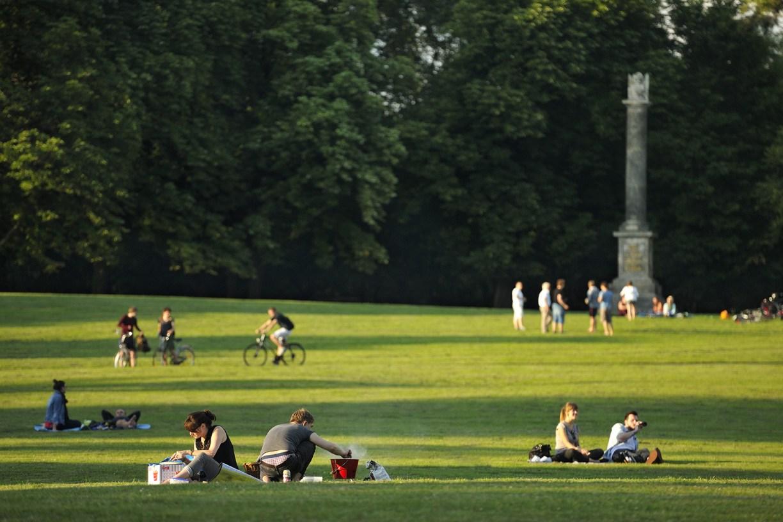 Wohin in Niedersachsen zum Outdoor Grillen. Junge Menschen im Prinzenpark, im Vordergrund ein Paar, das den Grill vorbereitet. BBQ Die schönsten Grillplätze in Niedersachsens Städten