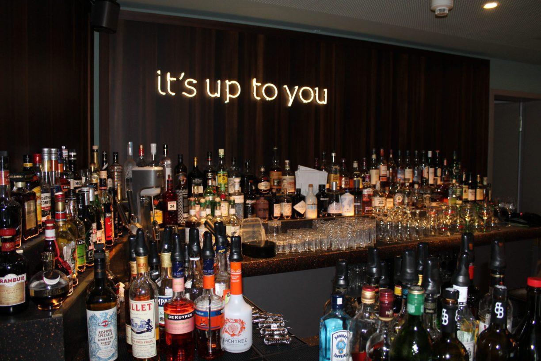 Eine Bar mit leuchtendem Schriftzug it's up to you