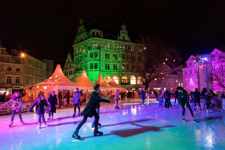 Schlittschuhläufer auf der bunt beleuchteten Eisfläche mitten auf dem Kohlmarkt. Winteraktivitäten
