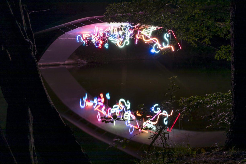 Bunte Neonröhren hängen unter einer Brücke. Sie spiegeln sich im Wasser.