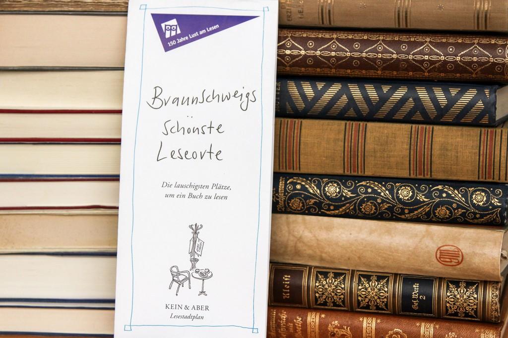 """Eine zusammengeklappte Stadtkarte mit dem Titel """"Braunschweigs schönste Leseorte"""" steht angelehnt an einem Stapel alter Bücher."""