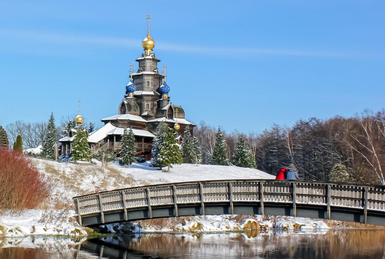 Russisch-Orthodoxe Holzkirche in winterlicher Schneelandschaft, davor die Holzbrücke über die Ise Richtung Mühlenmuseum