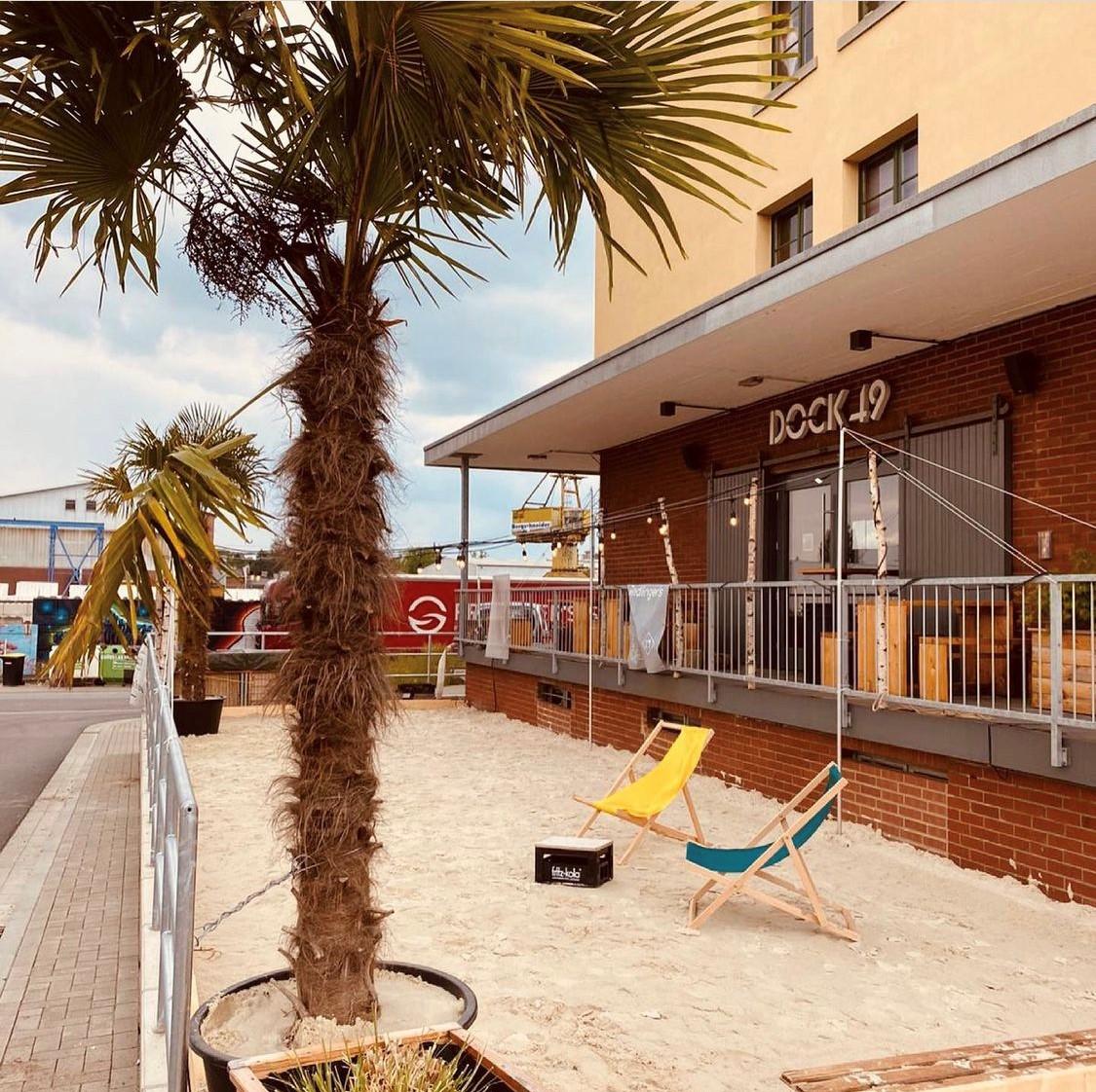 Strandbar vor dem Dock49: Auf der mit Sand aufgeschütteten Terasse stehen zwei bunte Beach Chairs, eine Palme und ein Kasten Bier. Im Hintergrund sieht man die Hafenkräne