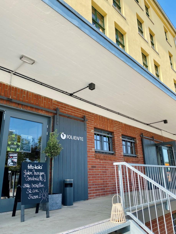 Eingang zum Mellow's & Joliente im Leisen Speicher mit Willkommensgruß auf der Tafel und Außenterasse