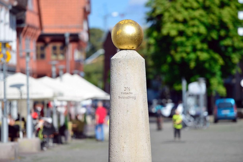 Der Meilenstein mit goldener Kugel und Entfernungsangabe in der Gifhorner Fußgängerzone