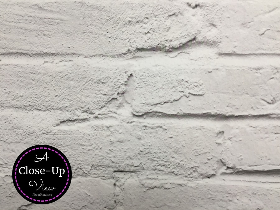 A close up view of a white brick wall mural shows all the texture in the bricks and mortar. Brick wallpaper sold by AboutMurals.ca.